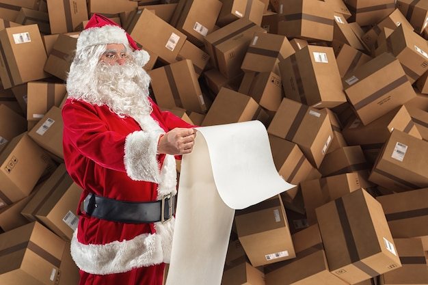 サンタクロースはプレゼントのリクエストと配達用の箱でいっぱいです