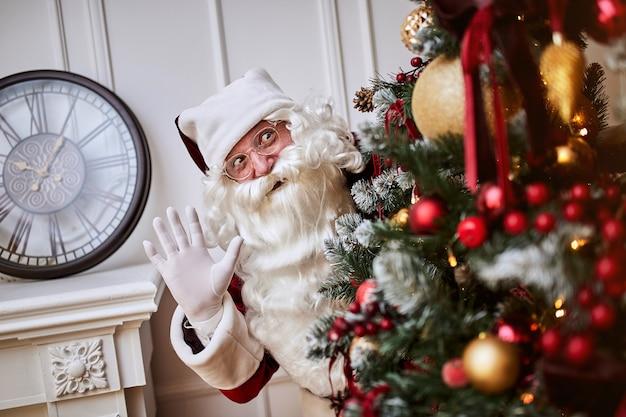 산타 클로스는 선물을 숨기기 위해 크리스마스 트리 뒤에 숨어 있습니다.