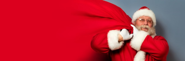 산타 클로스는 그의 어깨에 거대한 선물 가방을 들고 있습니다. copyspace. 크리스마스 기적, 축하 및 선물 개념.
