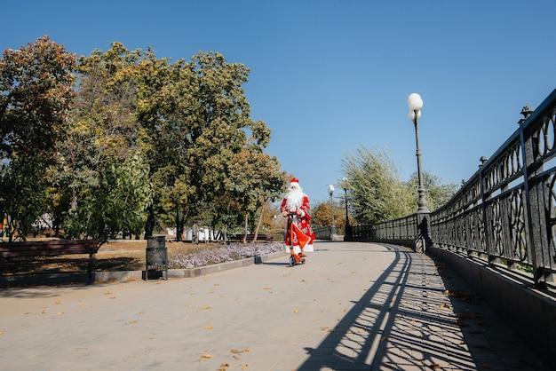 Дед мороз спешит на самокате с подарками к празднику детям.