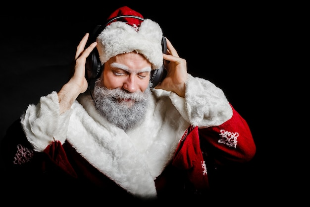 Santa claus is listening to music with headphones on a black background
