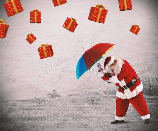 산타 클로스는 우산을 든 선물로 보호됩니다.