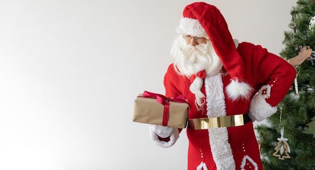 산타 클로스는 크리스마스 트리 근처에 서서 선물 상자를 들고 그것을보고 있습니다.