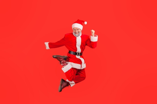 Santa claus jumping to air with happy excited expression, celebrating winter holidays.