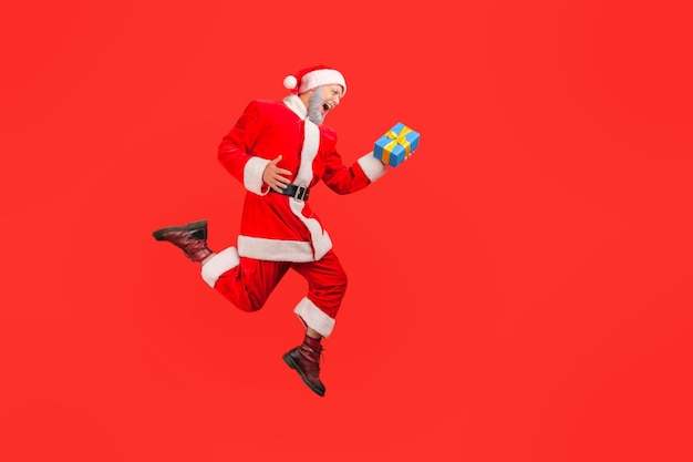 Santa claus jumping in air with present box, celebrating christmas holidays.