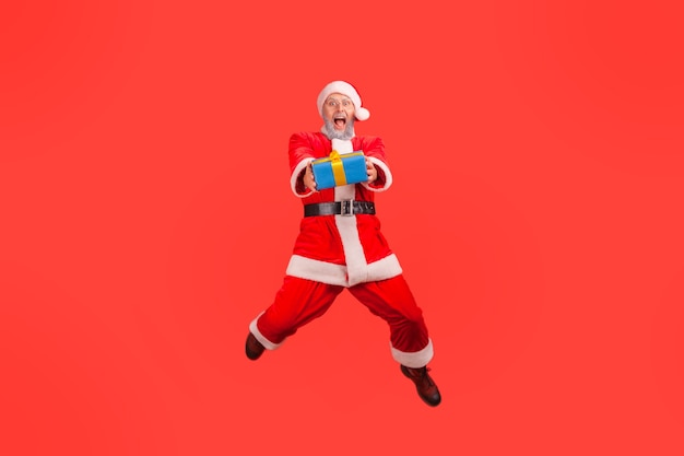 Santa claus jumping high with wrapped present box, giving gift for christmas, looking at camera.