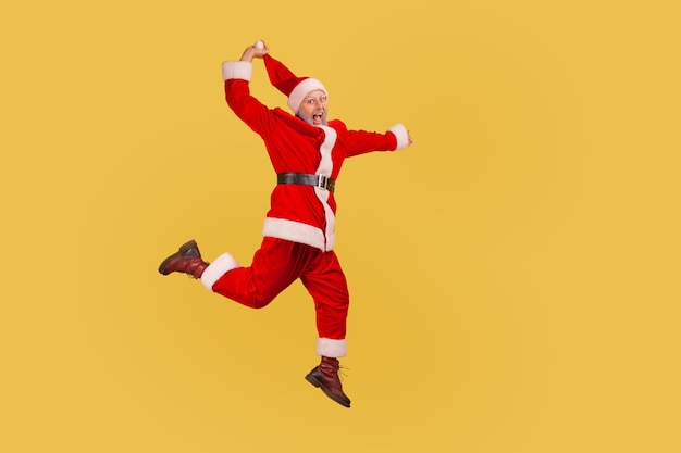 Santa claus jumping up high and pulling his red hat, celebrating christmas with excitement.