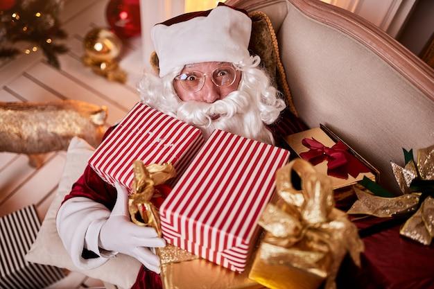 산타 클로스는 벽난로와 크리스마스 트리 근처에서 선물을 잔뜩 들고 소파에 누워 휴식을 취합니다. 새 해와 메리 크리스마스, 해피 홀리데이 개념