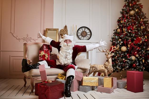 산타 클로스는 벽난로와 크리스마스 트리 근처에 선물을 잔뜩 들고 소파에 누워 있습니다.