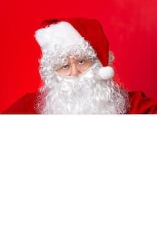 산타 클로스 복사 공간이 빨간색 배경에 고립 된 빈 화이트 보드 뒤에서 찾고