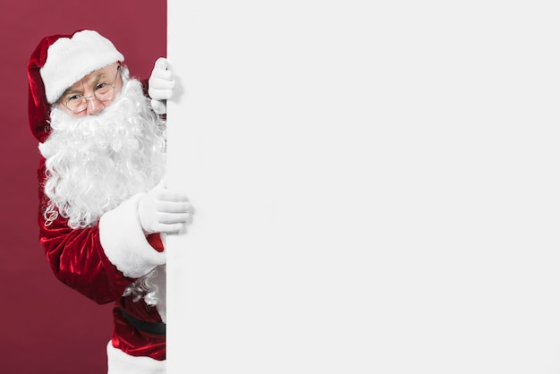 Santa claus looking out of white wall