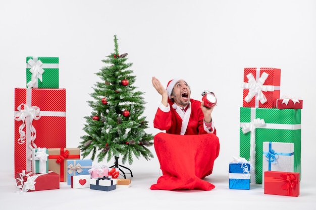 Santa claus looking above sitting in the ground and showing clock near gifts and decorated xmas tree