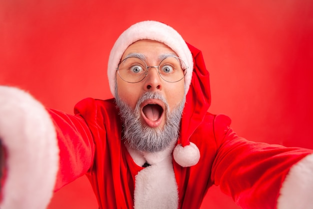 Santa claus making selfie pov or broadcasting live stream from christmas party, excited expression.