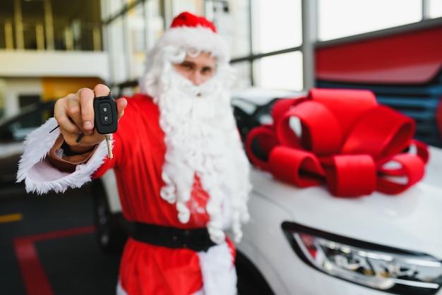 Santa claus near a new car in a car dealership.