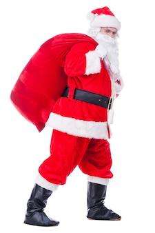 이동 중인 산타클로스. 흰색 배경에 대해 걷는 동안 선물과 함께 자루를 들고 카메라를 찾고 전통적인 산타 클로스의 전체 길이