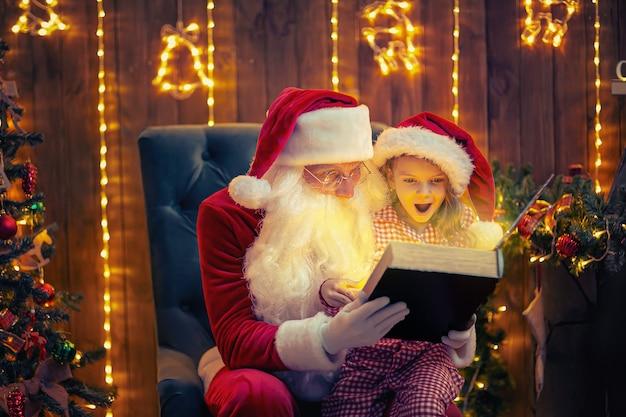 산타 클로스는 파자마에 귀여운 놀란 소녀와 마법의 책을 열고 읽습니다.
