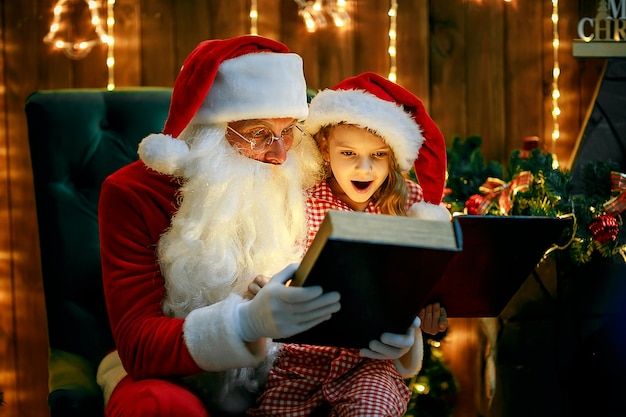Santa claus open and read magic book with little cute amazed girl in pajama