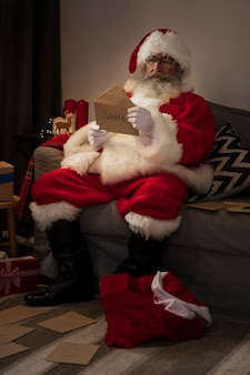 Santa claus opening a letter from a kid