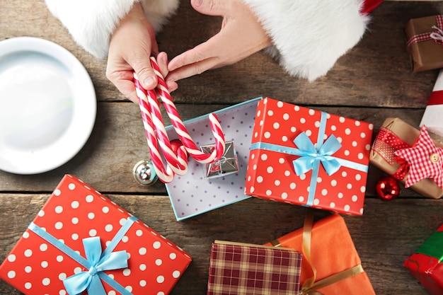 Santa claus packing candy into gift box, close up