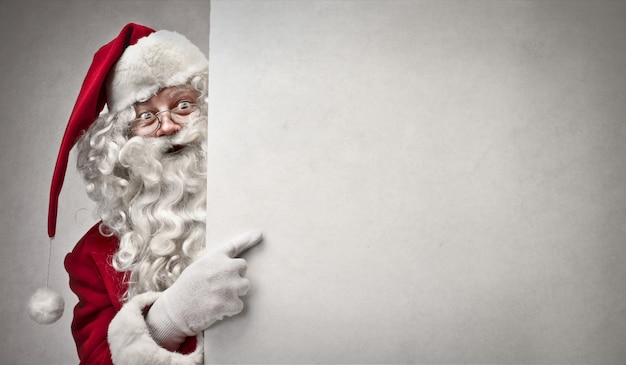 Santa claus pointing on a board