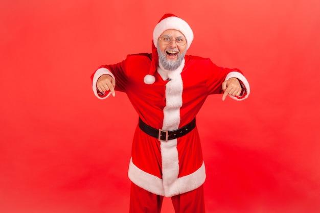 サンタクロースが指で下を向いて、アイデアのプレゼンテーション、コマーシャルテキストの場所を示しています。