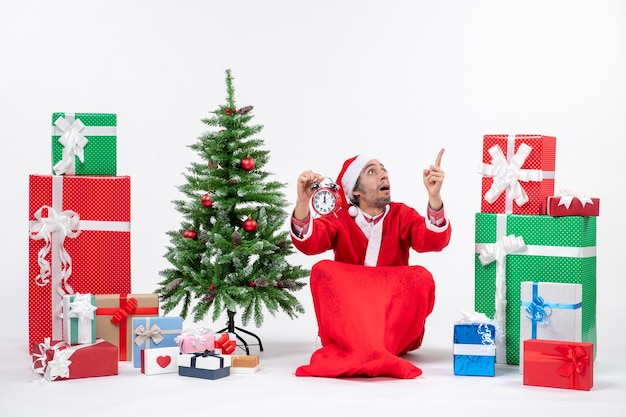 Santa claus pointing above sitting with gift boxes and tree