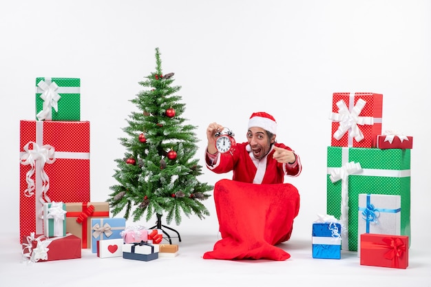 Santa claus pointing something sitting in the ground and showing clock near gifts and decorated xmas tree