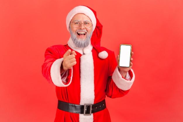 Санта-клаус указывая на камеру и показывая смартфон с пустым экраном.