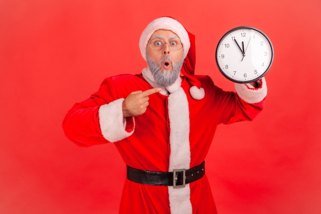 Santa claus pointing at wall clock waiting for appointment, keeping mouth open.