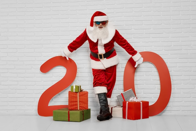 Santa claus posing at camera with presents and numbers of 20