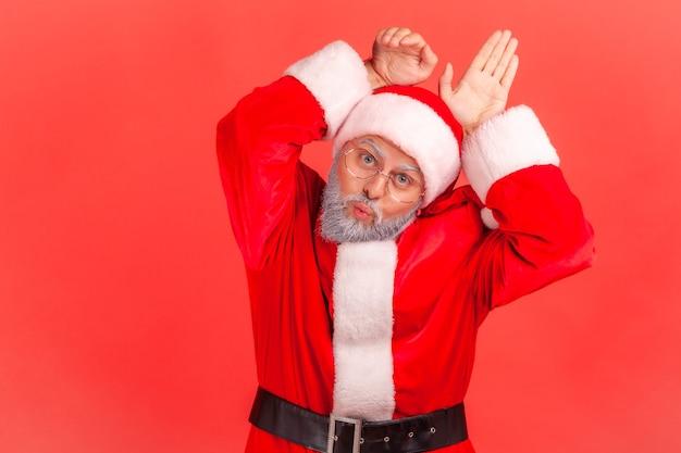 장난스럽게 입술을 내밀고 토끼 귀를 내밀고 있는 산타클로스는 코믹한 유치한 얼굴을 하고 있다.