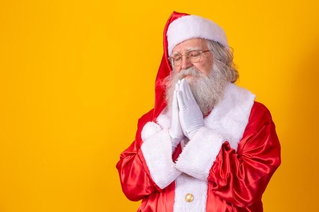노란색 배경에 기도하는 산타클로스. 믿음