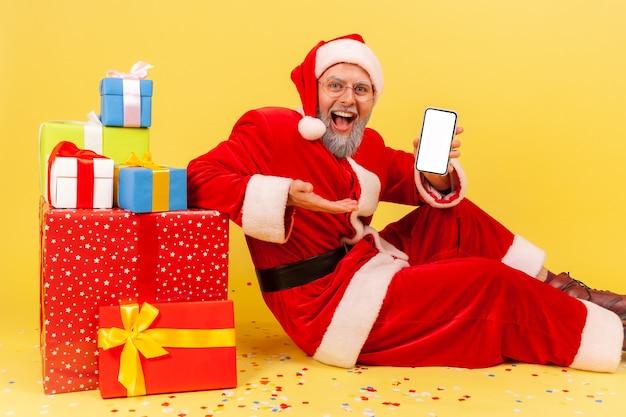 Санта-клаус, представляя пустой белый дисплей сотового телефона, сидя рядом с новогодними подарочными коробками.