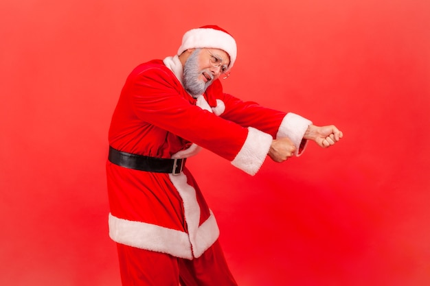 Santa claus pretending to pull invisible rope, concept of hard working,