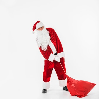 Santa Claus pulling sack of gifts