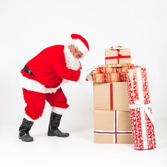 Santa claus pushing pile of wrapped presents