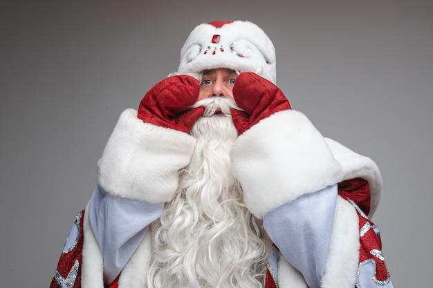 Дед мороз положил руки ко рту, чтобы спросить или поздравить кого-то, студийный праздничный портрет на сером