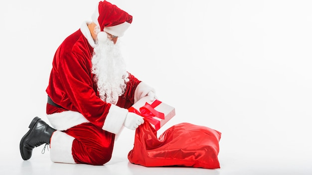 Santa claus putting gift box in sack