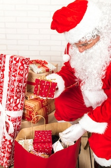 Santa claus putting gift boxes into big sack