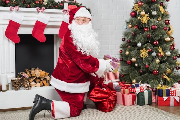 산타 클로스 크리스마스 트리 아래 선물을 퍼 팅