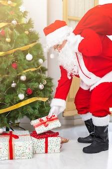전나무 나무 아래 선물을 퍼 팅하는 산타 클로스