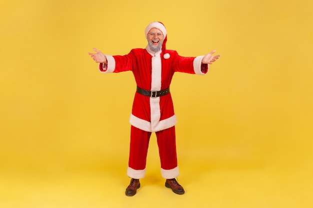 포옹하기 위해 손을 들고 환영하고 미소 짓는 산타 클로스는 회의에 기뻐합니다.