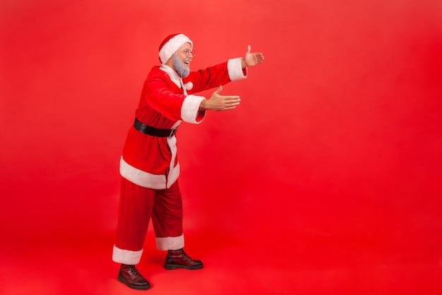 산타 클로스가 손을 내밀고 누군가를 안기 위해 팔을 뻗습니다.