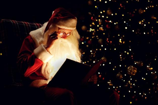 暗い部屋に座って魔法の本を読んでいるサンタクロース