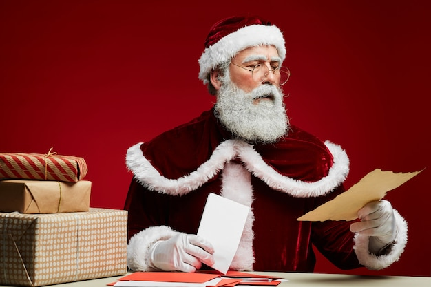 Santa claus reading letters on red