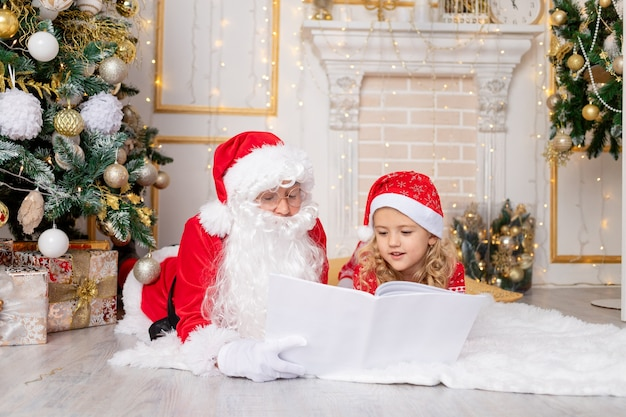 サンタクロースはクリスマスツリーで子供の女の子に本を読みます