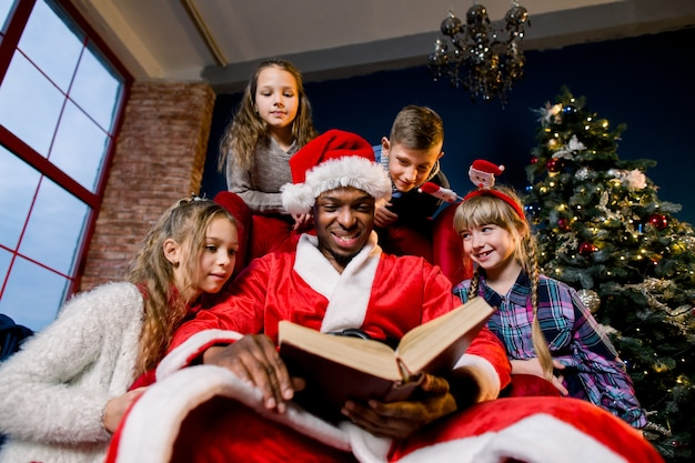 サンタクロースは赤い椅子の周りに座っている子供たちのためにクリスマスの物語の本を読みます