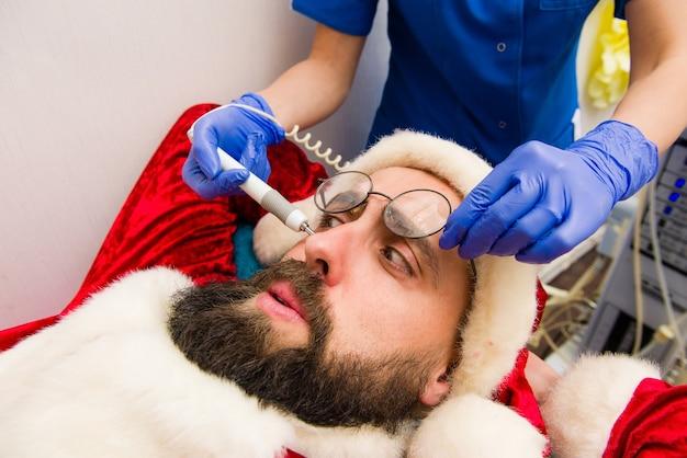 Santa claus receiving facial beauty treatment.