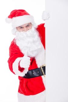 산타클로스가 추천합니다. 복사 공간 밖을 내다보며 엄지손가락을 치켜드는 쾌활한 산타클로스