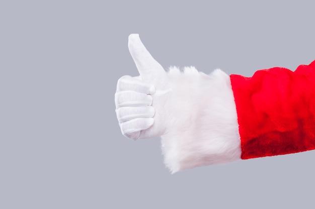 산타클로스가 추천합니다. 회색 배경에 자신의 엄지손가락을 보여주는 산타 클로스의 근접